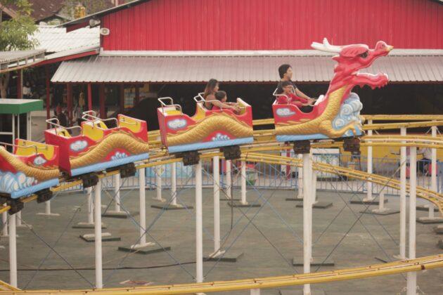 Beberapa pengunjung yang sedang menikmati wahana dragon coaster di Blitar park
